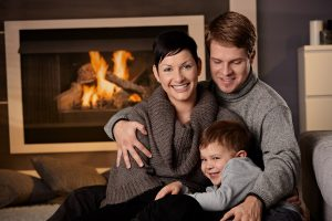 Photo of a happy family with a working furnace and fireplace