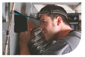 Man Inspecting Ductwork