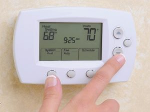 adjusting thermostat in your home